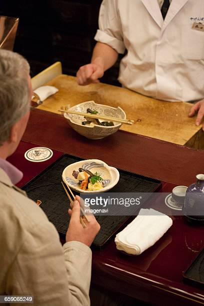 Mature Caucasian man eating Japanese dishes