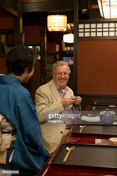 Mature Caucasian man talking with Japanese hostess