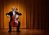 Mature cellist playing on stage infront of curtains