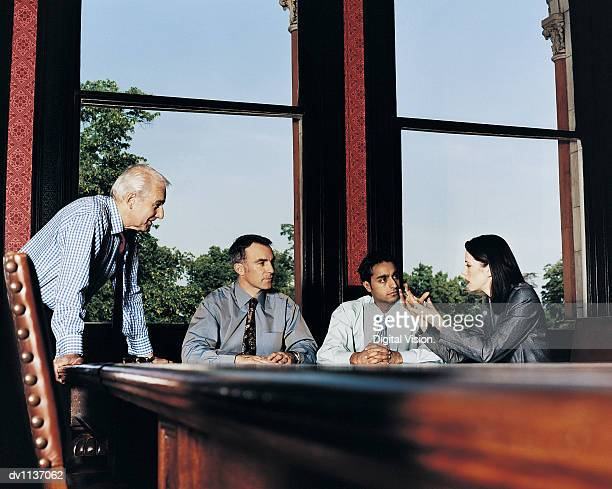 Mature CEO and Business Colleagues in Discussion in a Conference Room