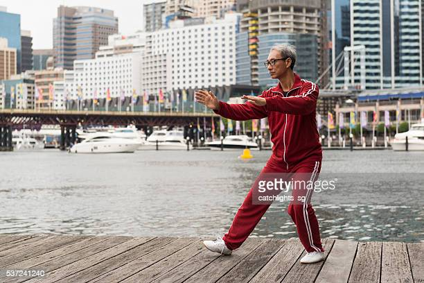Mature Chinese Man Practising Tai Chi Chuan on Quay Side