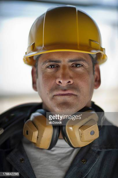 Mature construction worker wearing hard hat and ear defenders