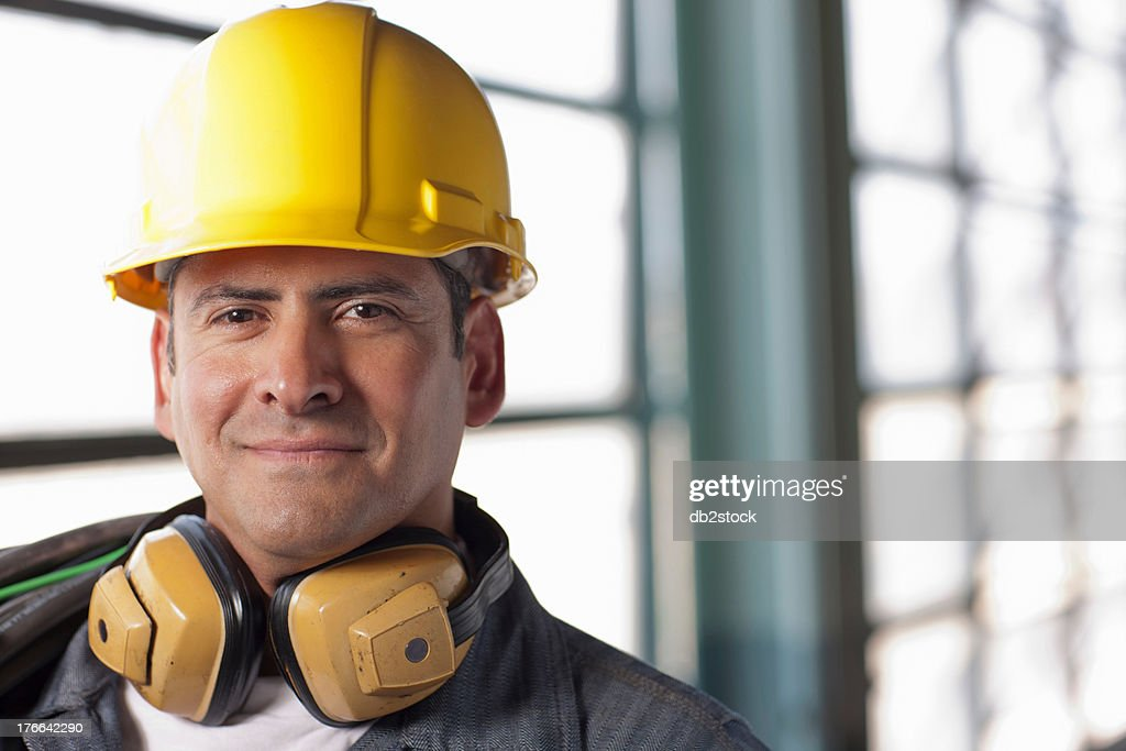 Mature construction worker wearing hard hat and ear defenders, smiling : Stock Photo