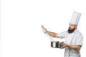 Mature cook whisking smth in a saucepan isolated on a white background. Space for text