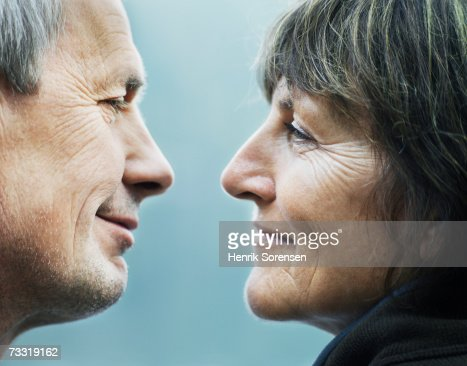 Mature couple about to kiss outdoors, profile