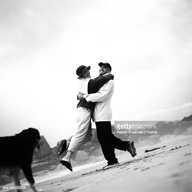 Mature couple and dog on beach, woman jumping into man's arms, b&w.