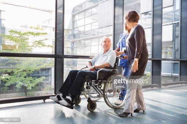 Couple d'âge mur et infirmière dans les couloirs