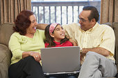 Mature couple and their granddaughter in front of a laptop