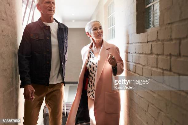 Mature couple arriving to rental flat, with suitcases and bag