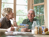 Mature couple at breakfast table, man holding postcard, smiling