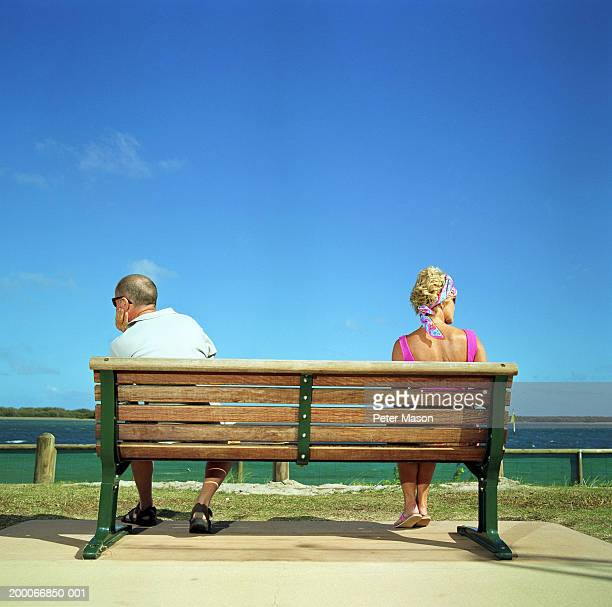 Mature couple at opposite ends of bench outdoors, rear view