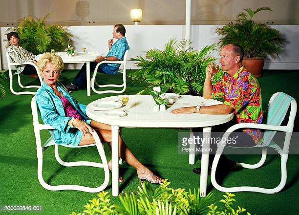 Mature couple at table on artifical lawn