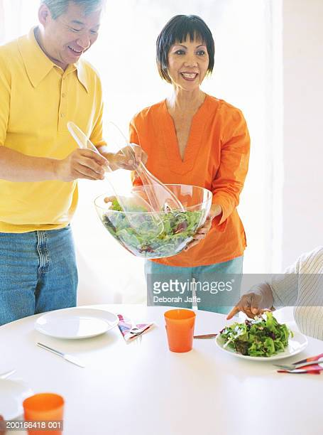Mature couple at table serving salad