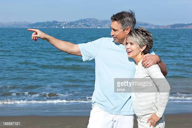 mature couple at water's edge, pointing to the distance