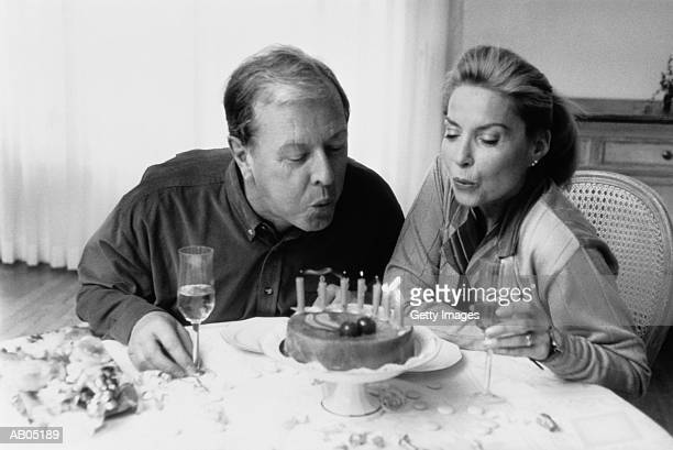 Mature couple blowing candles on cake (B&W)
