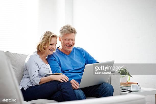 Mature couple browsing internet on laptop