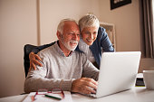 Mature couple browsing the internet and buying. Online shopping.