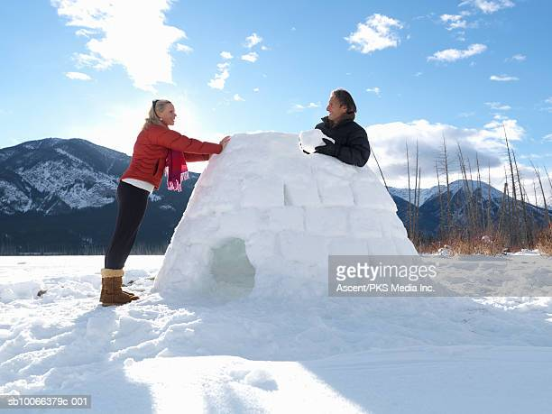 Mature couple building igloo on snow covered lake, smiling