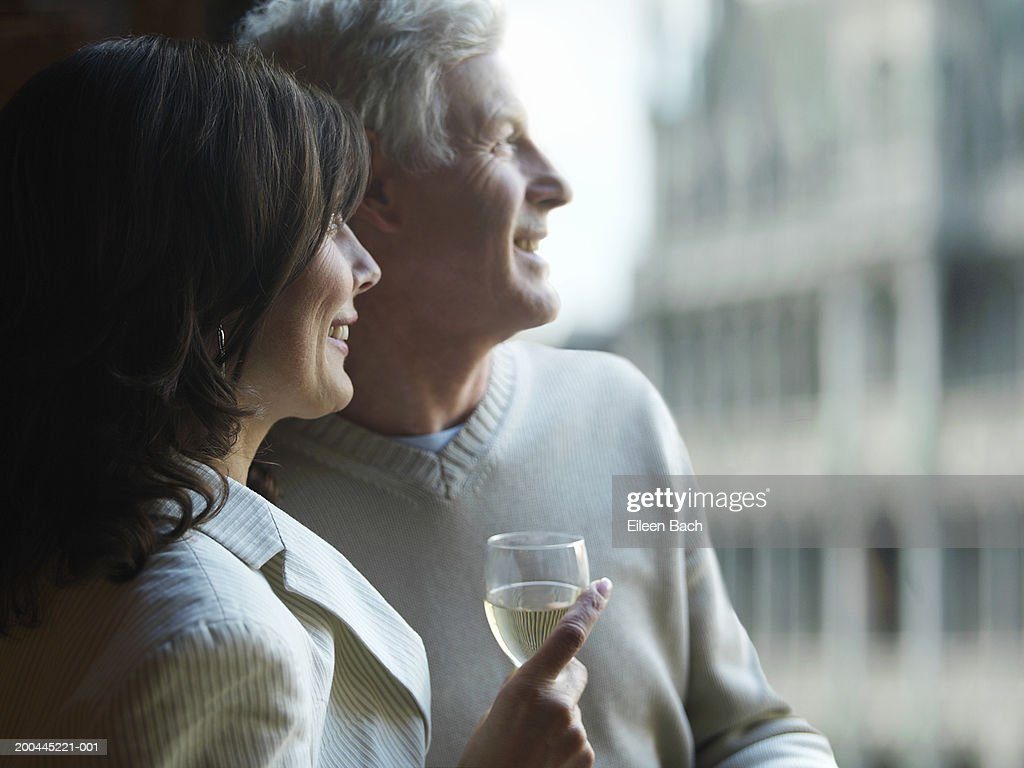 Mature couple by window, woman holding glass of wine, smiling : Stock Photo