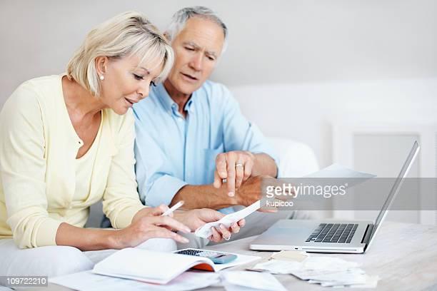 couple d'âge mûr calcul frais avec un ordinateur portable sur une table