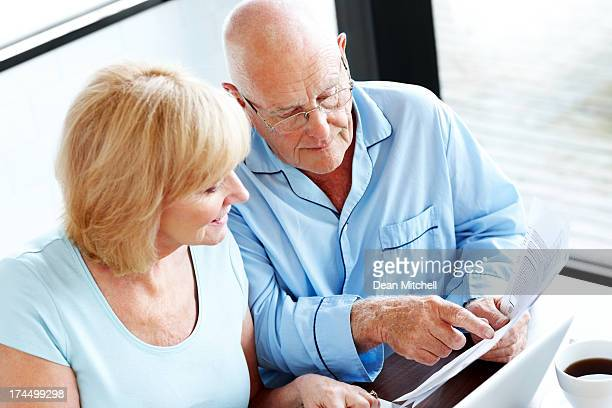 Mature couple calculating their monthly expenses