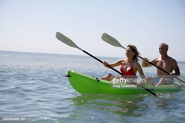 Mature couple canoeing in bay, smiling