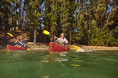 Portrait of a mature couple canoeing on a lake during a camping trip. Active senior couple in two single kayaks in the lake.