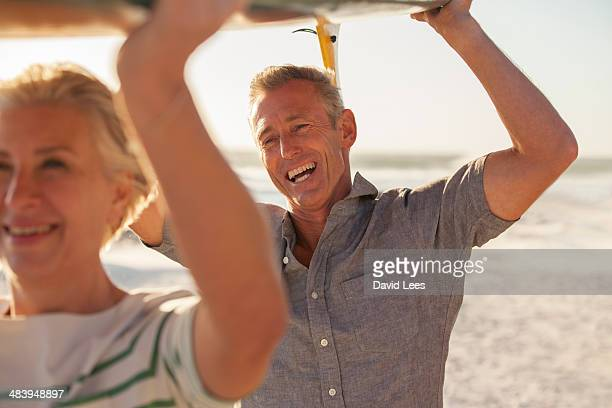Mature couple carrying surfboard on beach
