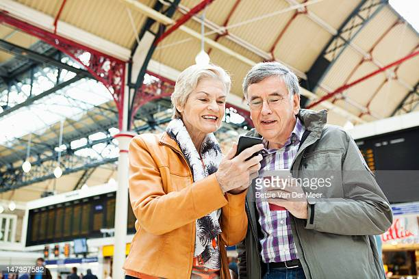 Mature couple checking messages on i phone.