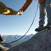 Mature couple climbing mountain, woman holding man's hand