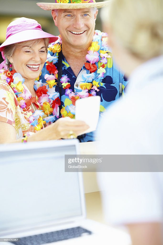 Mature couple collecting an airline ticket at reception counter : Stock Photo