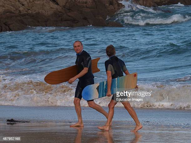 Mature couple coming out of the sea after bellyboard surfing St Ives Cornwall UK