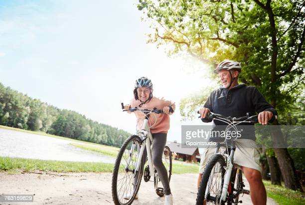 Mature couple cycling beside lake, laughing, low angle view