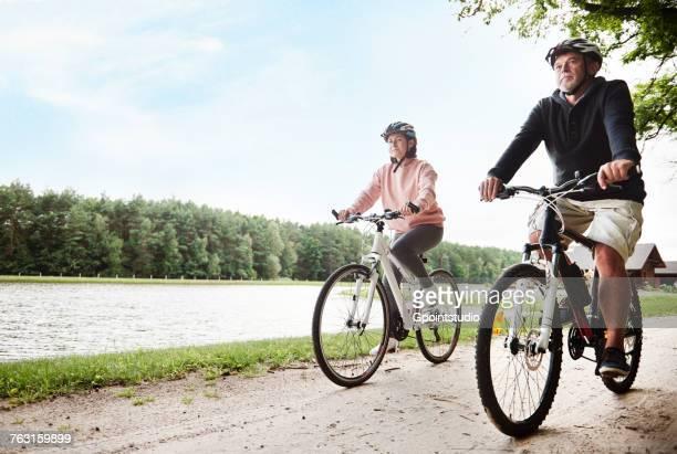 Mature couple cycling beside lake