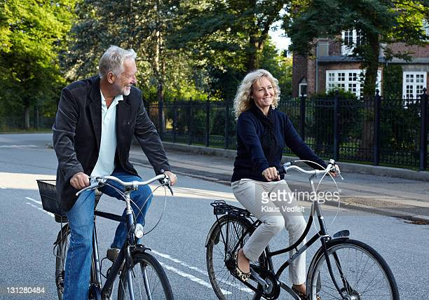 Mature couple cycling in residential neighborhood