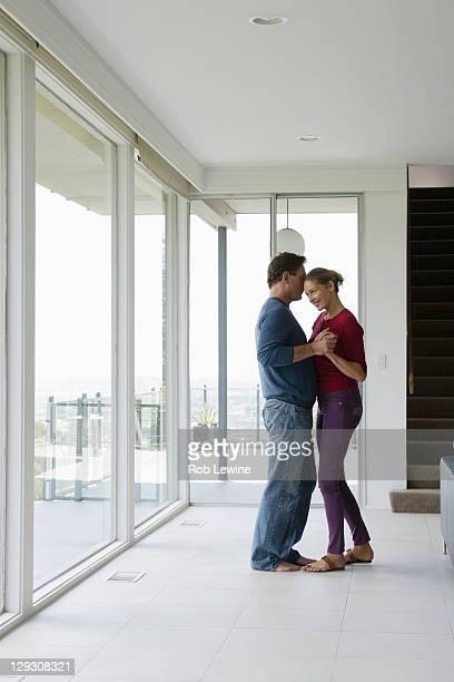 Mature couple dancing in empty living room