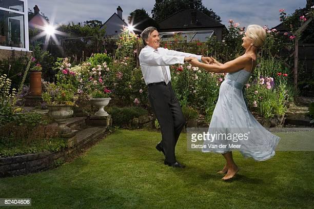mature couple dancing in garden.