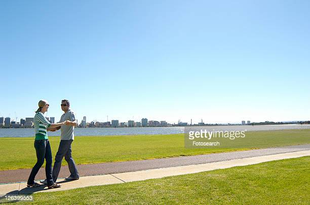 Mature couple dancing in park with city in background, Perth, Australia