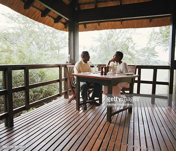 Mature couple dining on lodge verandah