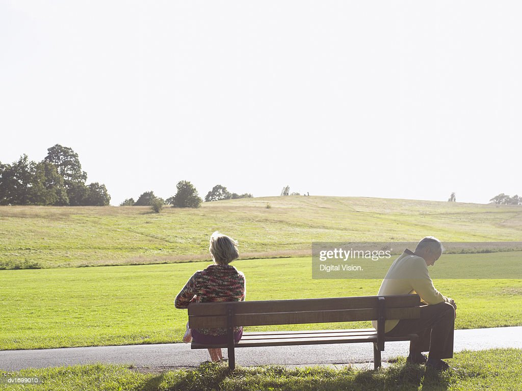 Mature Couple Displeased With each Other Sitting on a Bench in Park : Stock Photo