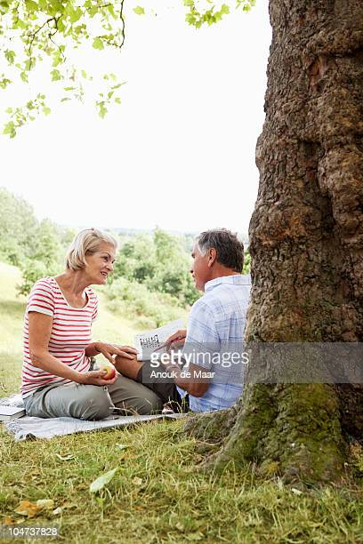 Mature couple doing crosswords in park