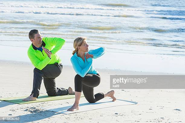 Mature couple doing yoga on the beach