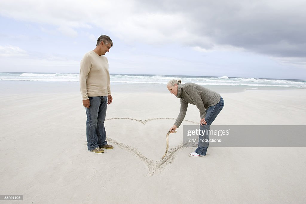 Mature couple drawing heart in sand at beach