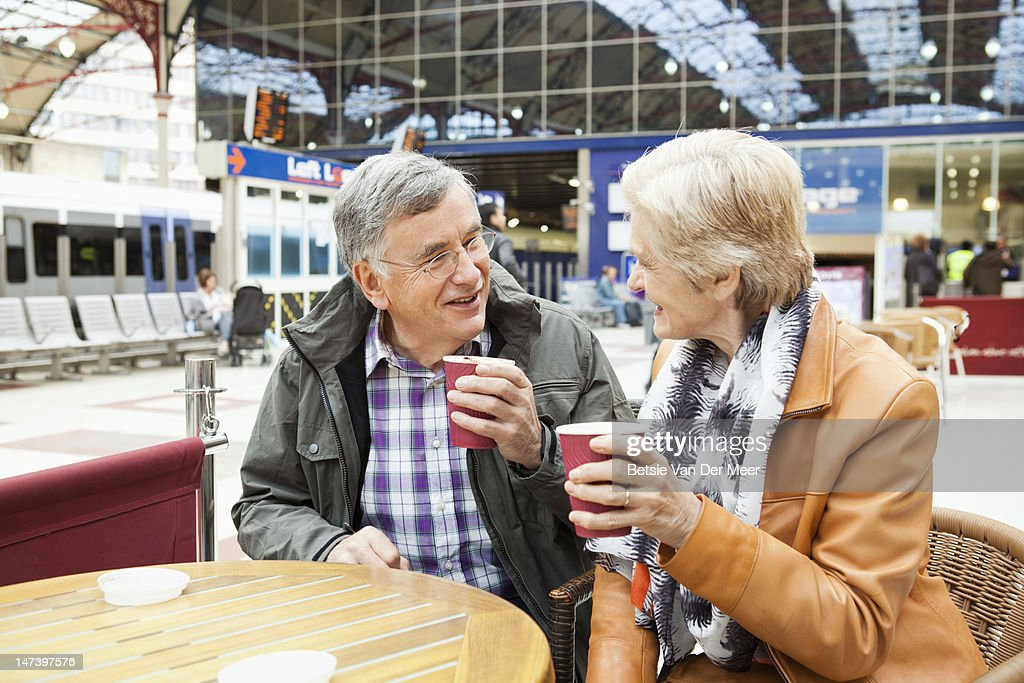 mature couple drinking coffee at railway station. : Stock Photo