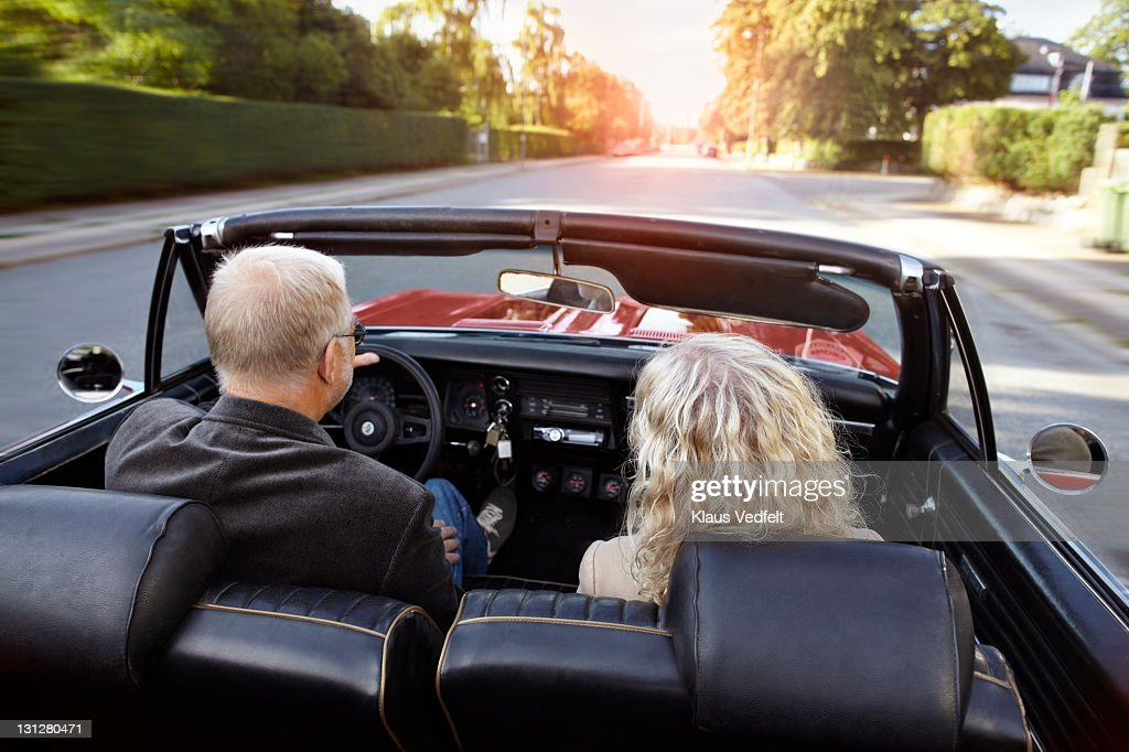 Mature couple driving convertible car in sunset : Stock Photo