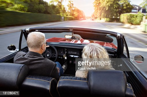 Mature couple driving convertible car in sunset : Foto stock