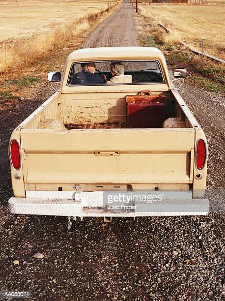 Mature couple driving pick-up truck on gravel road, rear view