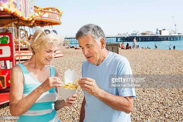 Mature couple eating chips on beach.