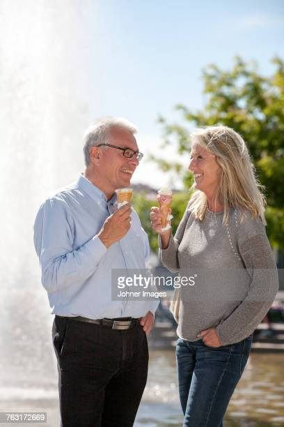 Mature couple eating ice creams in park