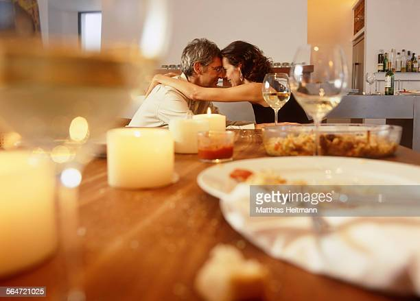 Mature Couple Embracing at Dinning Table